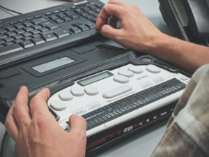 Photograph depicts a visually disabled person operating a computer using a Braille screenreader.